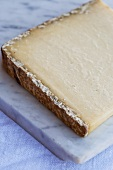 A piece of Cantal cheese on a marble slab