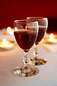 Two glasses of red wine on a candle lit table