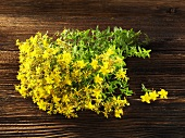 Flowering St. Johns wort on a wooden surface