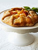 Peach galette on a cake stand