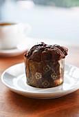 A mini chocolate muffin in a paper case
