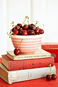 A bowl of cherries on a stack of old cook books