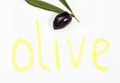 An olive and the word 'olive' written in olive oil