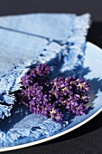 A blue plate with a fabric serviette and lavender flowers