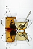 Tea in two different glass cups with infusers