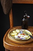 Herring salad and beer on a wooden chair