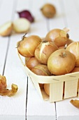 Brown onions in a wooden basket