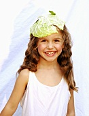A girl with a cabbage leaf on her head