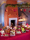 A Christmas buffet in a decorated room in front of an open fire