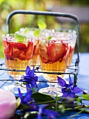 Glasses of strawberry punch with lemon balm and ice cubes