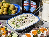 A buffet with various herring dishes and dill potatoes