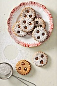 Linzer Augen (nutty shortcrust jam sandwich biscuits with holes on top) with icing sugar