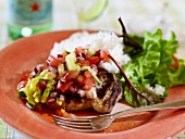 A pork chop with tomato salsa, rice and a green salad