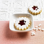 Linzer biscuits (nutty shortcrust jam sandwich biscuits with holes on top) with redcurrant jam