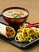 Chinese dishes (fried noodles, a wrap with vegetables and vegetable soup)