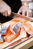 Salmon fillets being cut into pieces