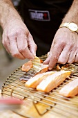Skin being removed from grilled salmon fillets