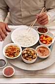 A man eating rice with various spicy dishes (Asia)