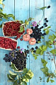 Berries, peaches, grapes and leaves on wooden background