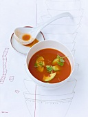 Tomato soup with avocado and chilli salsa, ladle