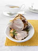 Roast pork, partly carved, with gravy in gravy boat