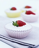 Yoghurt cream with strawberries in four paper cases