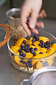 Hand scattering blueberries into a bowl for peach gratin