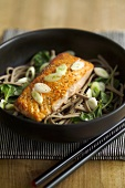 Fried salmon on soba noodles and vegetables in a dish