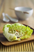 Sprout salad in a lettuce leaf on a wooden board