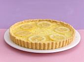 A lemon tart on a cake plate