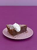Ein Stück Schokoladen-Mandel-Torte mit Schlagsahne