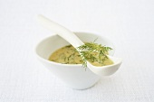 A dish of mustard and dill sauce with china spoon
