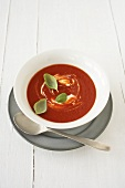 A plate of tomato soup with basil leaves