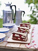 Three pieces of Black Forest gateau & coffee out of doors