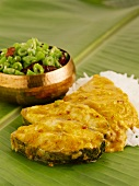 Fish curry with beans and rice on banana leaf (India)