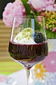 A glass of berry compote with yoghurt and basil
