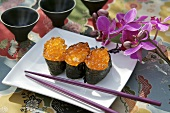 Three maki sushi with salmon caviar