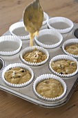 Filling muffin tin with banana & chocolate muffin mixture