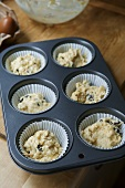 Muffin mixture with dried cherries in a muffin tin (UK)