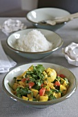 Chicken curry with vegetables, coriander leaves & dish of rice