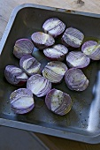 Seasoned, halved red onions on baking tray