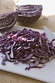 Shredded red cabbage with knife and chopping board