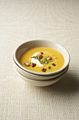 A bowl of pumpkin cream soup with herb croutons