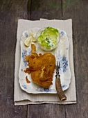Half a fried chicken with lettuce on wooden background