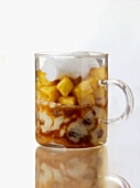 Pineapple in honey & sake with coconut foam in a glass mug