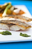 Fried sea bass with pesto and vegetables