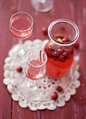 Cranberry liqueur in a carafe and glasses