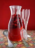 Home-made cranberry liqueur in a glass carafe