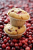 Two cranberry muffins, one on top of the other on cranberries