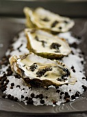 Three oysters with butter sauce & caviar on a bed of salt